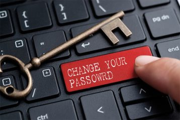 An image featuring a person pressing a red custom key on a keyboard that says change your password