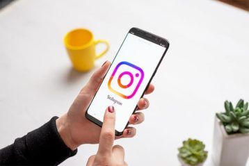An image featuring a person holding their phone and using Instagram
