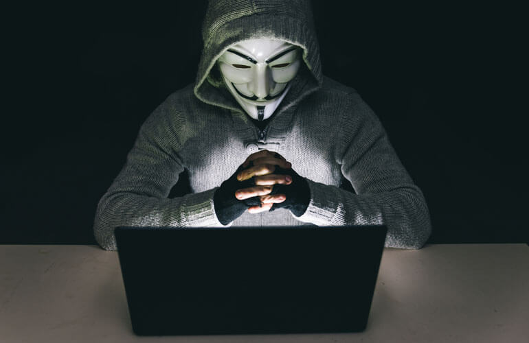 Man With anonymous association mask working on the laptop