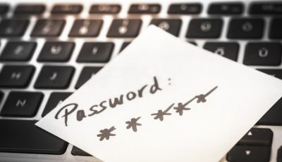 """a sticky note lying on keyboard with """"password *****"""" written on it"""