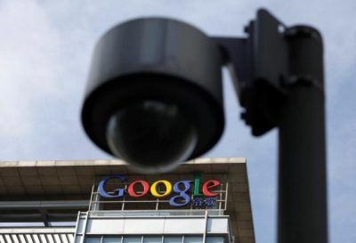 The Google logo is seen on the top of its China headquarters building, behind a road surveillance camera in Beijing