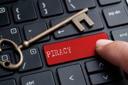 a golden key and a person pressing a red key on a computer keyboard with the word piracy