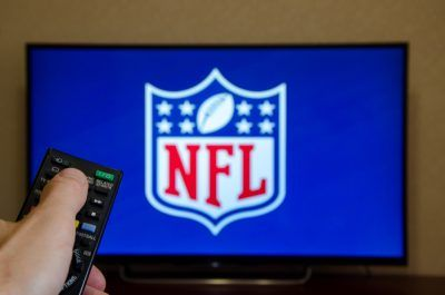 Man holding remote control to watch NFL game.