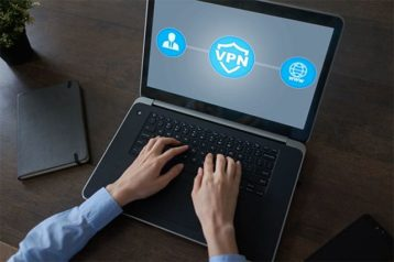 An image of a person using a laptop that has a VPN logo on the monitor