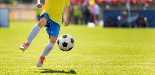 An image of a football player in a yellow shirt kicking a football on a playing field