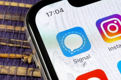 an image of the signal application showcased on an iphone device's screen in a blue color with a white chat bubble in the middle and an outline