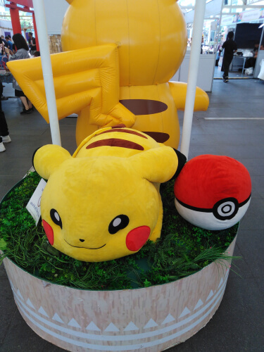 an enormous pikachu plushi with a pokeball on the side