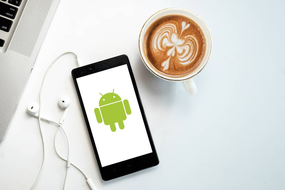 andriod phone placed right beside coffee cup