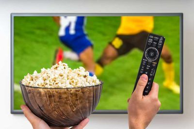 Man watchng football on TV with remotecontrol and popcorn in his hands.