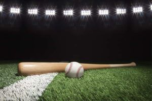 Baseball and bat at night under stadium lights on grass field with white stripe.