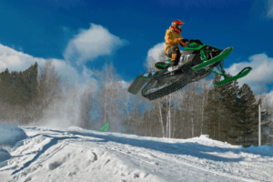 Snow mobile jumping in the snow