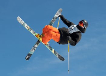 Skiier doing a big jump with crossed ski