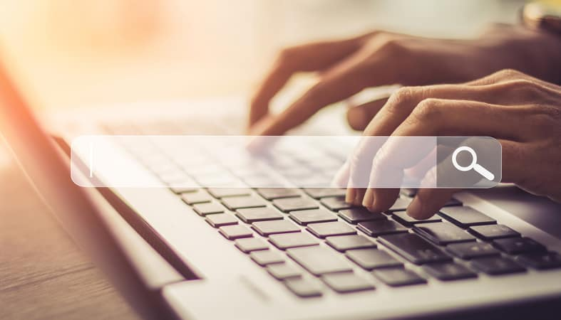 an image of a person's hands typing on a grey laptop with black keys with a transparent search bar on top