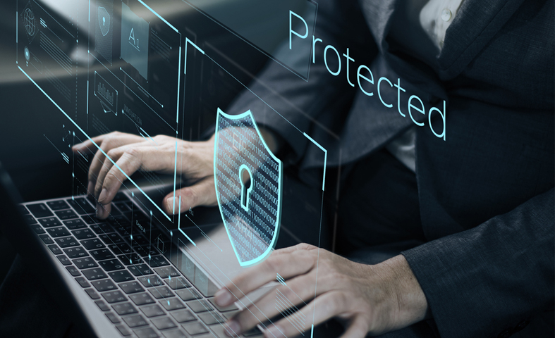 an image of a man sitting in front of a laptop with a suit while a simulated logo and the word Protected is shown