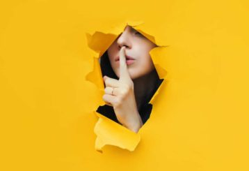 a yellow background with a hole in the middle where a woman comes out and points a finger at her mouth which implies you should shut up