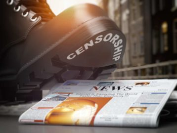 an image of a boot crushing a newspaper
