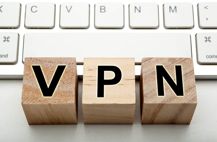 blocks of wood with the letters VPN on them in front of an Apple keyboard