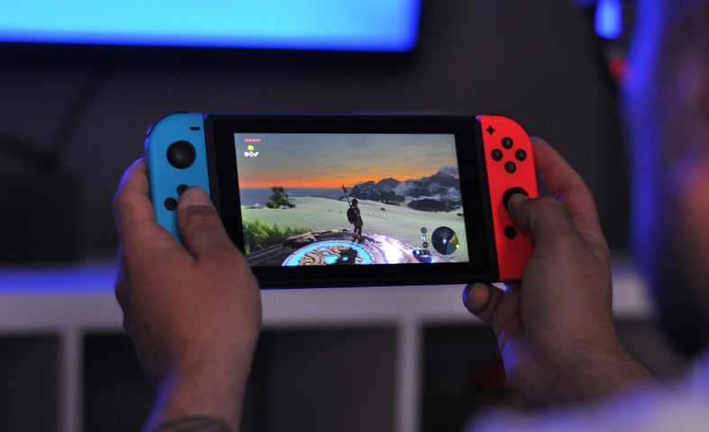 an image of a person holding a nintendo switch playing the legend of zelda breath of the wild