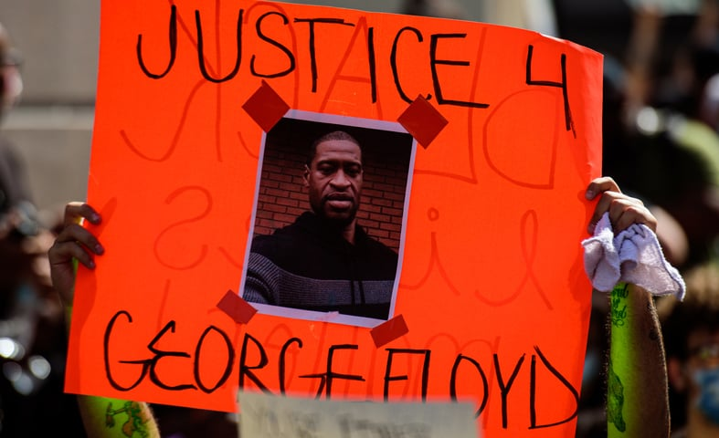 A person holding up an orange sign with the image of George Floyd with the words Justice 4 George Floyd on it