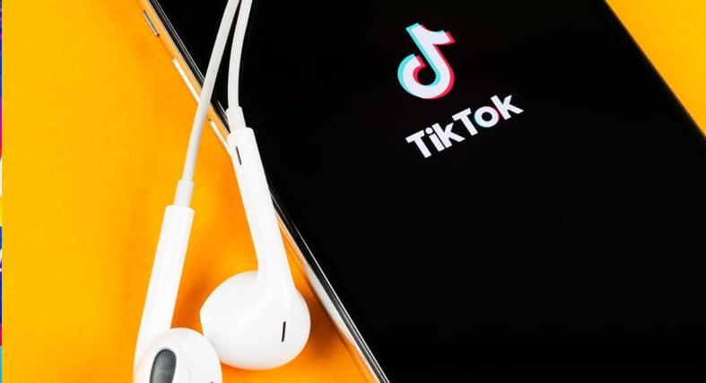 a phone running TikTok with headphones