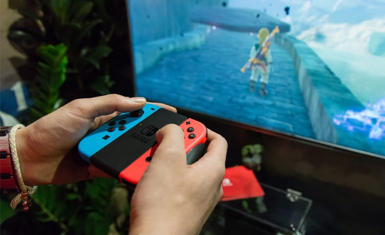 person playing nintendo switch on docked mode