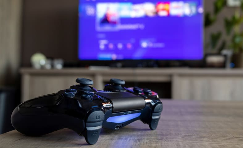 An image of a ps4 controller in front of a television