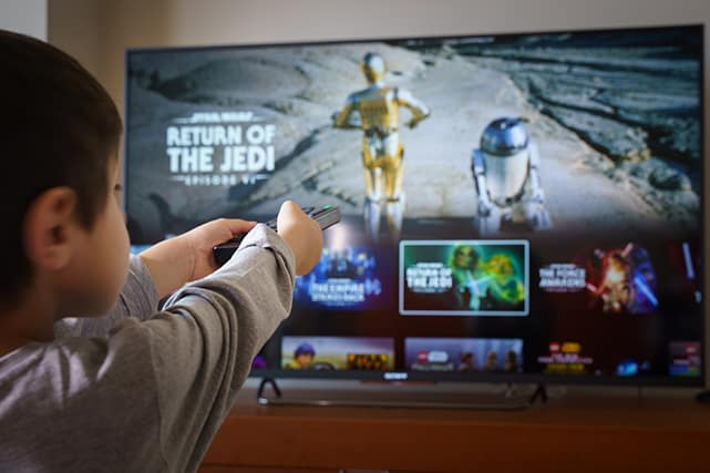 a child attempting to stream star wars in front of a television