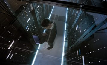 a male software engineer working inside of a server room