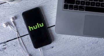an image of hulu running on an iphone next to a macbook