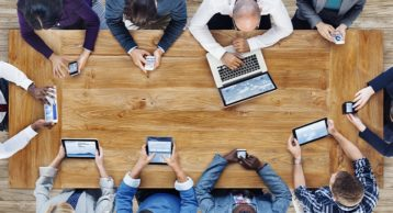 an image of people in a room on a desk using a multitude of devices