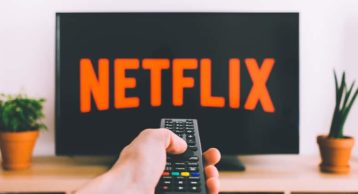 an image of a person watching Netflix with a remote control