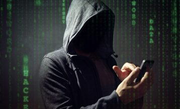 an unknown person in a hoodie using a smartphone to hack a system