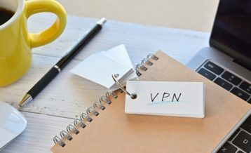 the word vpn drawn on a notebook that is sitting on a laptop next to a black pen and a yellow cup filled with dark coffee