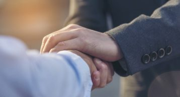 an image of two people shaking hands in suits indicating trust