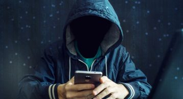 an image of a person in a hoodie using a smartphone