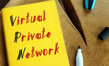 virtual private network drawn with black and red letters on top of a yellow notebook which is on top of a wooden log