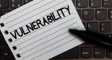 an image showcasing a vulnerability note on top of a laptop