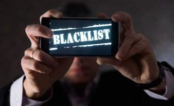 a man holding up a smartphone with Blacklist on the screen