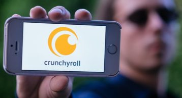 man holding up an iphone with the crunchyroll logo