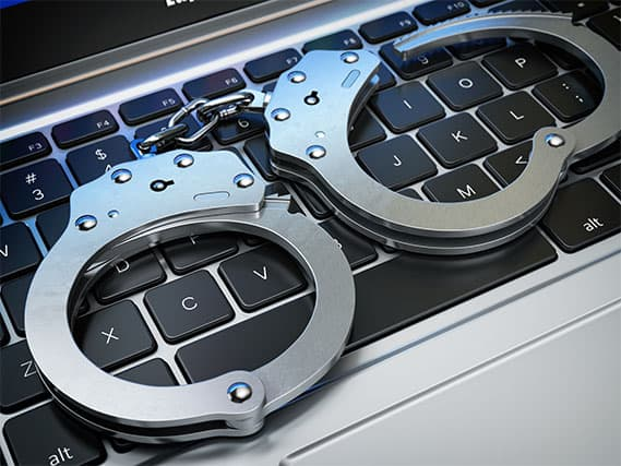 An image featuring a keyboard with handcuffs on top of it representing piracy lawsuit