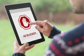 An image feautring a person using his tablet and opening his ad blocker