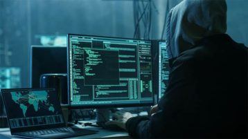An image featuring a person using his computer and laptop for hacking representing a cybercrime hacker