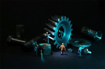 An image featuring cogs and screws and builders representing an database maintenance