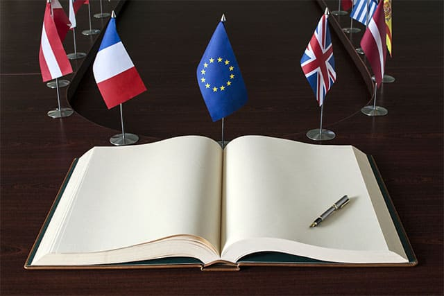 An image featuring a open book with European flags in the background representing the Europe commission report