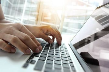 An image featuring a person using his laptop