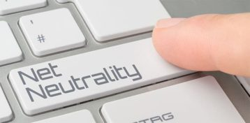 An image featuring a person pressing the enter button that has a text that says net neutrality