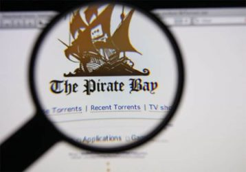 An image featuring someone using a magnifying glass on the pirate bay website