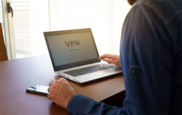 An image featuring a person using his laptop while connected to a VPN service