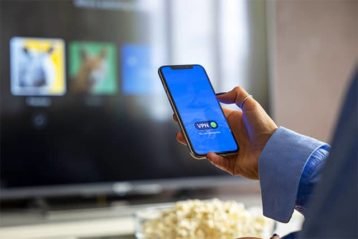 An image featuring a person holding his phone and is streaming to his television
