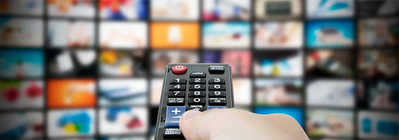 An image featuring a person holding out his TV remote and accessing multiple channels on TV